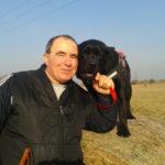 Egy férfi a mezőn egy szalmabála mellett áll. A szalmabálán a fekete színű labrador vakvezető kutyája áll. Arca hozzáér a kutya pofájához.