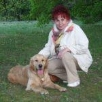 Egy őszi hűvös napon egy erdő melletti mezőn egy hölgy térdel golden retreiver kutyája mellett.