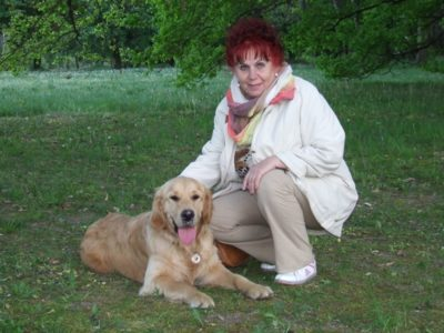 In the picture there is an elderly lady squatting with her guide dog, a Golden Retriever, lying beside her.