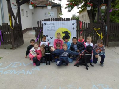 In the picture children are squatting in front of the school fence with Diamond and Fanni, the two black Labradors.