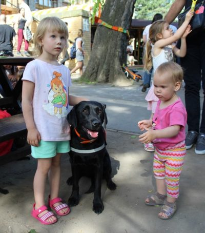 A guide dog is sitting in the picture. A little girl is standing next to him, stroking his head. Another little girl is also standing on the other side of the dog a little further.