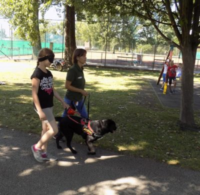 In the picture a black guide dog is leading a girl. The dog's leash is held by her trainer .