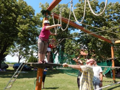 In the picture a young woman is satnding on a wooden ramp. She is grabbing the first of the hanging loops.