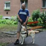 Egy társasház előtt egy férfi a zsemleszínű vakvezető kutyájával. A kutya éppen felnéz a gazdijára.