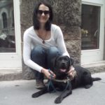 Egy fiatal hölgy leguggol a fekete színű vakvezető kutyája mellé, amelyik éppen fekszik és a kamerába néz.