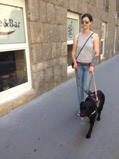 In the picture a visually impaired young woman is walking on the sidewalk with her black guide dog.