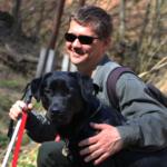 Egy férfi az erdőben, fehér bottal a kezében legugol a fekete labrador vakveztő kutyája mellé.