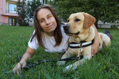 In the picture there is a young woman lying on the grass and hugging her guide dog, a yellow Labrador, who is lying beside her.