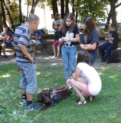 In the picture Csaba is standing, Bonca is lying in front of him in guide dog harness. Two schoolgirls are standing in front of them and another one is squatting beside Bonca.