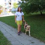 Egy hölgy a játszótérhez vezető járdán közlekedik a zsemleszínű vakvezető kutyájával