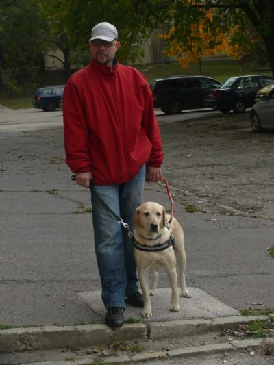 In the picture Krisztian and Nina, a yellow Labrador, are standing on the edge of the sidewalk.