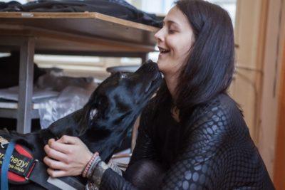 A képen Frutti a vakvezető kutya, aki egy fekete labrador és puszit ad gazdájának, Zsuzsinak.