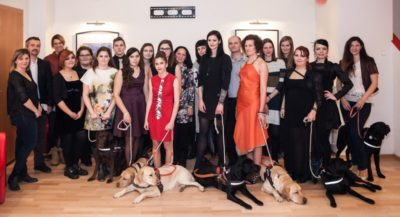 The image is a tableau showing the models, volunteers and guide dogs participating in the fashion show.