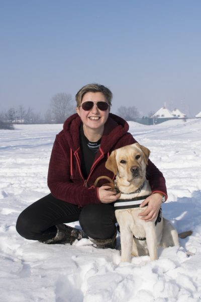 In the picture Erzsi is kneeling in the snow cuddling Gesztenye, a yellow Labrador, who is sitting beside her in harness