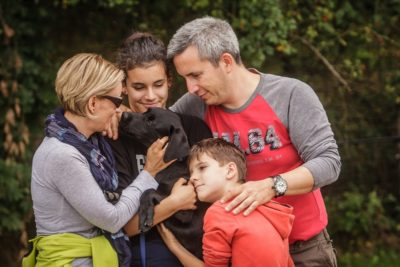 In the picture a family is hugging a black Labrador puppy.
