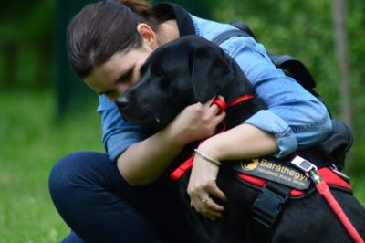In the picture Ani is embracing Felhő,  a black Labrador]