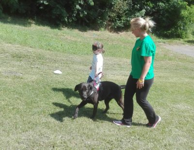 In the picture Bóbita, a black Labrador is guiding a little girl. Bobita's trainer is walking beside them.