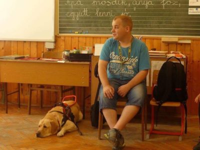 In the picture Milan is sitting on a chair and talking. His guide dog, Nelson, a yellow Labrador, is lying beside him on the ground.