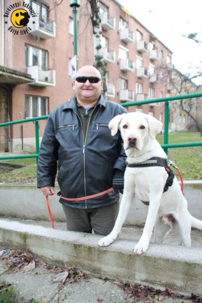 Kiss Barna áll, mellette egy padkára fellépve Gyömbér kutyája pózol a kamerának