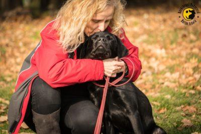 Kölyöknevelő önkéntesünk öleli át alapítványunk leendő vakvezető kutyáját, aki nála lakik és velünk tanul.