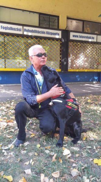 Csengeri István a fűben guggol Igorral a fekete vakvezető kutyájával