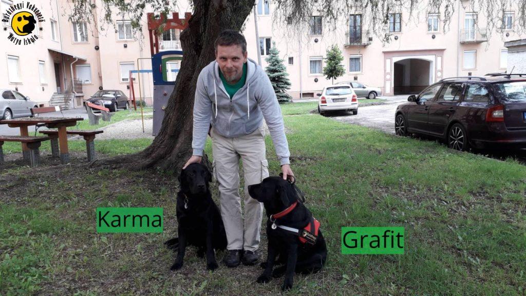 Karma és Grafit a fekete labradorok nyugodtan ülnek Lajos lábánál