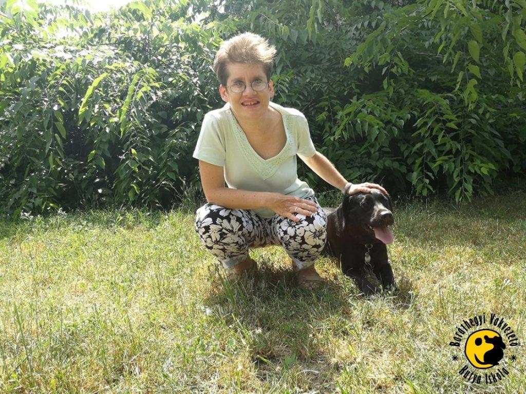 Inga büszkén fekszik a mellette guggoló Lilla lábánál