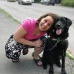 Egy fiatal barna hölgy egy forgalmas út melletti járdán guggolva odabújik a mellette ülő fekete labrador retreiver vakvezető kutyájához.