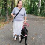 Írisz mellett áll fekete labradorja, Dolly egy parkban.