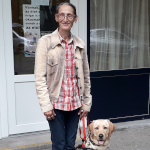 An elderly woman stands with her guide-dog with Bartáhegyi cover